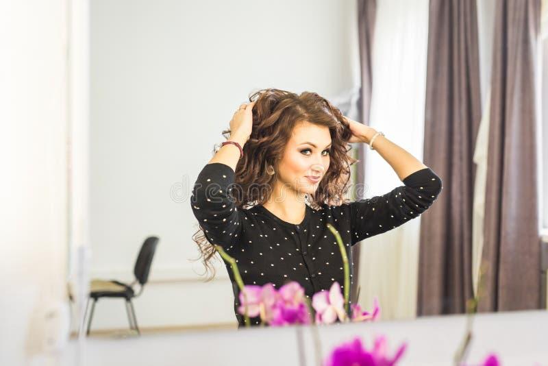 Skönhet-, frisyr- och folkbegrepp - lycklig ung kvinna med den fulländande frisyren på salongen royaltyfri fotografi