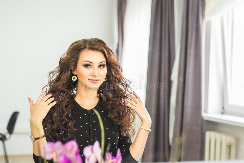 Skönhet-, frisyr- och folkbegrepp - lycklig ung kvinna med den fulländande frisyren på salongen arkivbild