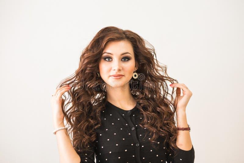 Skönhet-, frisyr- och folkbegrepp - lycklig ung kvinna med den fulländande frisyren på salongen arkivbilder
