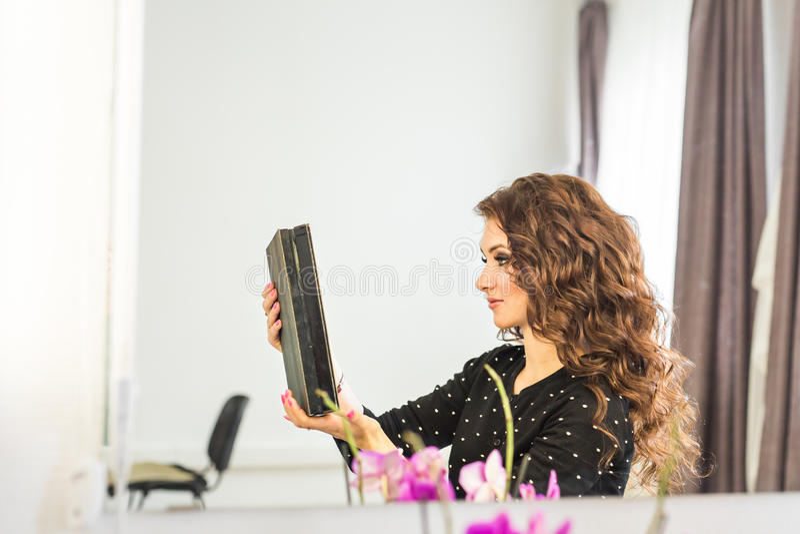 Skönhet-, frisyr- och folkbegrepp - lycklig ung kvinna med den fulländande frisyren på salongen royaltyfri bild