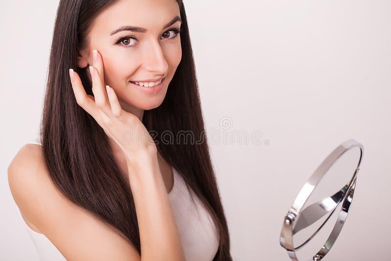 Skönhet, hudomsorg och folkbegrepp - le den unga kvinnan som applicerar kräm till framsidan och ser för att avspegla det hemmasta arkivfoton
