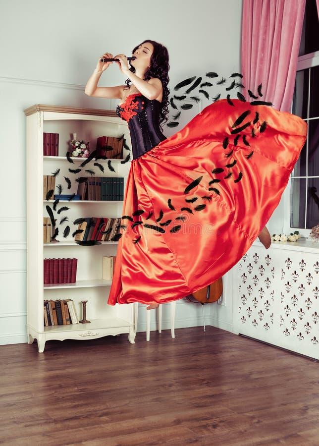 Skönhet i mitt--luft Fullt längdstudioskott av den attraktiva unga kvinnan i den orange klänningen som svävar i luft och att spel arkivfoton