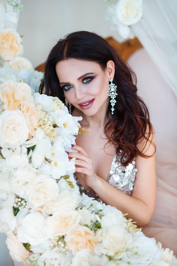 skönhet isolerad ståendewhite Härlig kvinna med sinnliga kanter som sitter bland vita blommor Skönhetsmedel smink parfymeriaffär arkivfoto