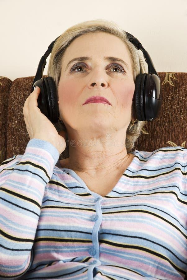 skönhet lyssnar musikpensionärkvinnan royaltyfria bilder