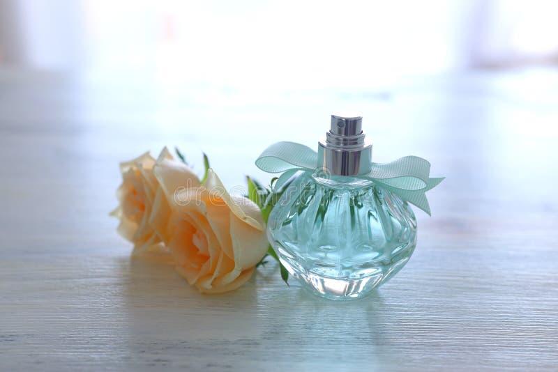Skönhet/modebild av den eleganta doftflaskan och delikata rosor över pastellfärgad bakgrund tappning filtrerad bild arkivbilder