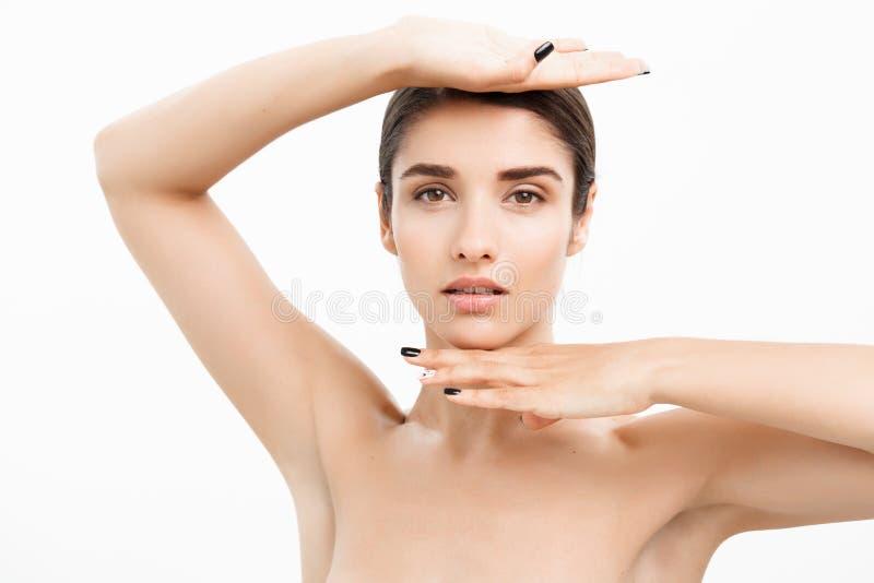 Skönhet- och hudomsorgbegrepp - nära övre härlig ung kvinna som trycker på hennes hud på vit bakgrund royaltyfria foton