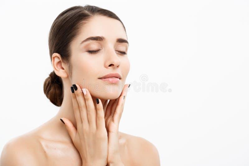 Skönhet- och hudomsorgbegrepp - nära övre härlig ung kvinna som trycker på hennes hud på vit bakgrund fotografering för bildbyråer