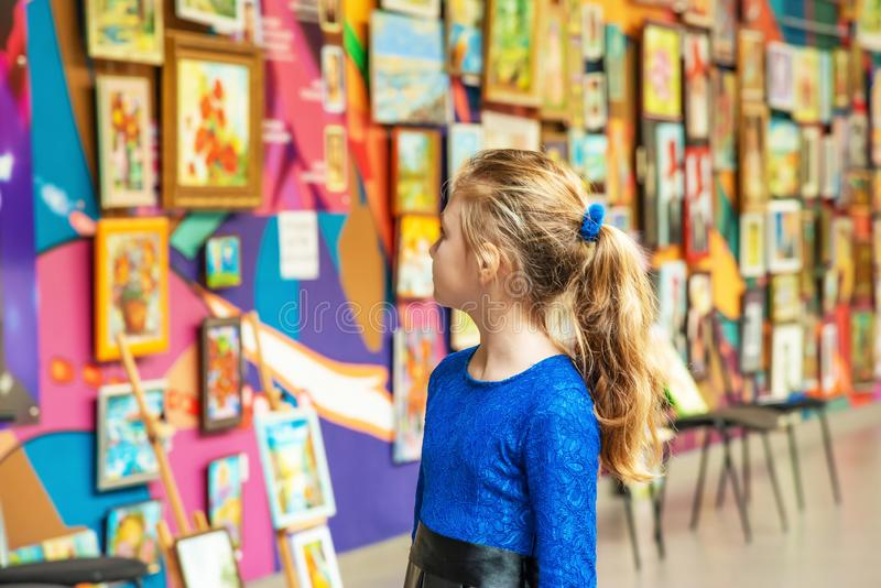Skönhet och noja drabbade en panikslagen beskåda konstnärlig konst för ung dam i folkkonstmuseer royaltyfri foto