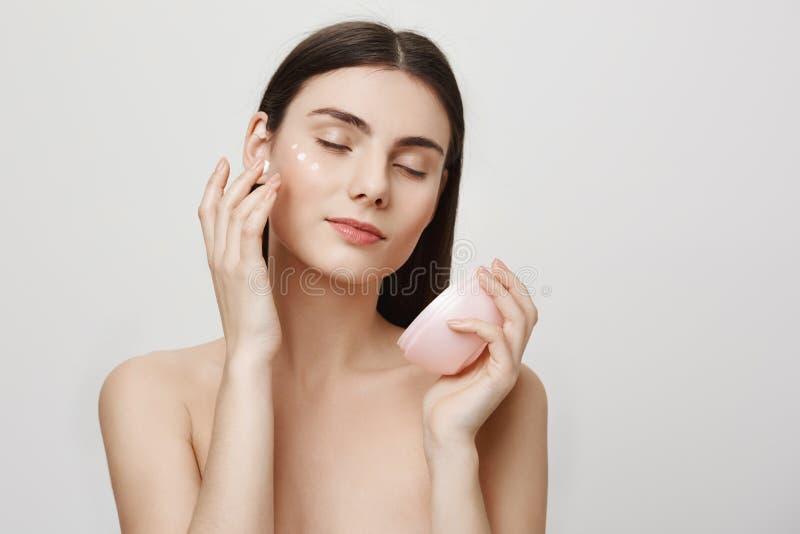 Skönhet och skincarebegrepp Studiostående av försiktig snygg europeisk kvinnagnuggbild i ansiktsbehandlingkräm som tycker om royaltyfri bild