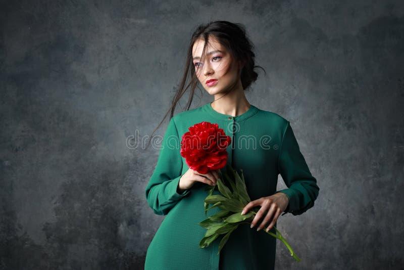 Skönhet, smycken, folk och lyxigt begrepp - härlig asiatisk kvinna i elegant klänning med pionblomman arkivfoto