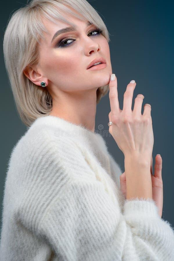 Skönhet, smycken och lyxigt begrepp - slut upp av den härliga unga kvinnan med örhängen på blå bakgrund royaltyfri fotografi