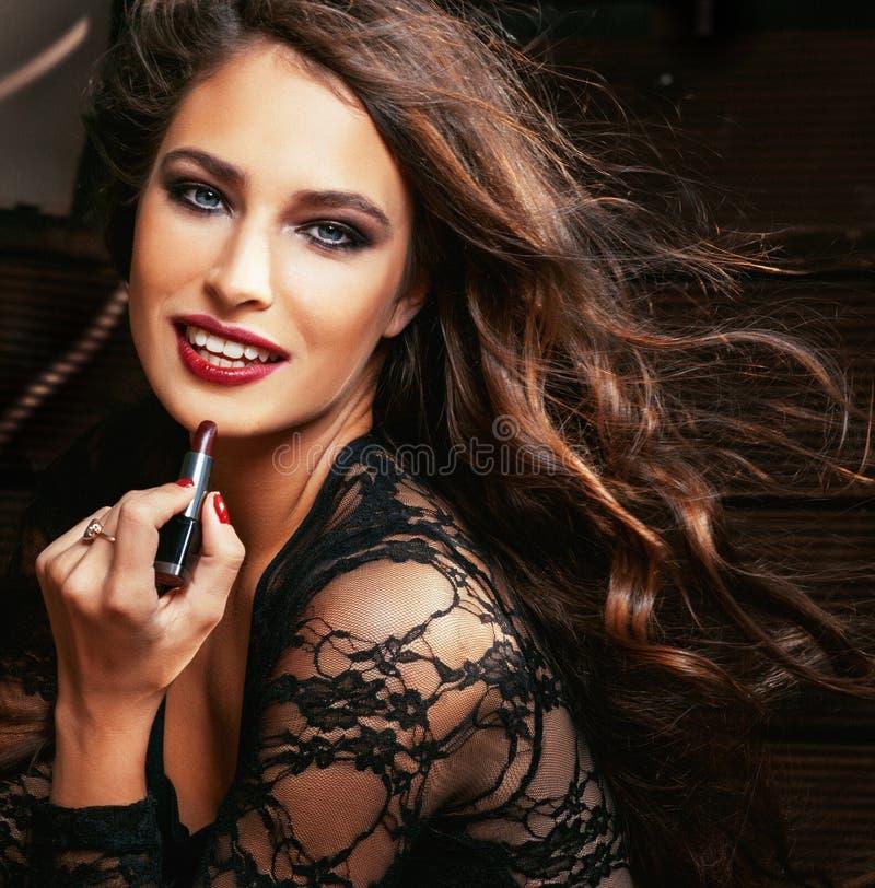 Skönhet som ler den rika kvinnan snör åt in, med mörker - röd läppstift arkivbilder