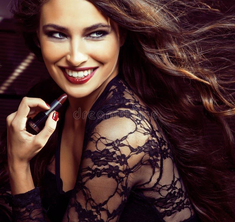 Skönhet som ler den rika kvinnan snör åt in, med mörker - röd läppstift som flyger upp hårslut royaltyfri foto