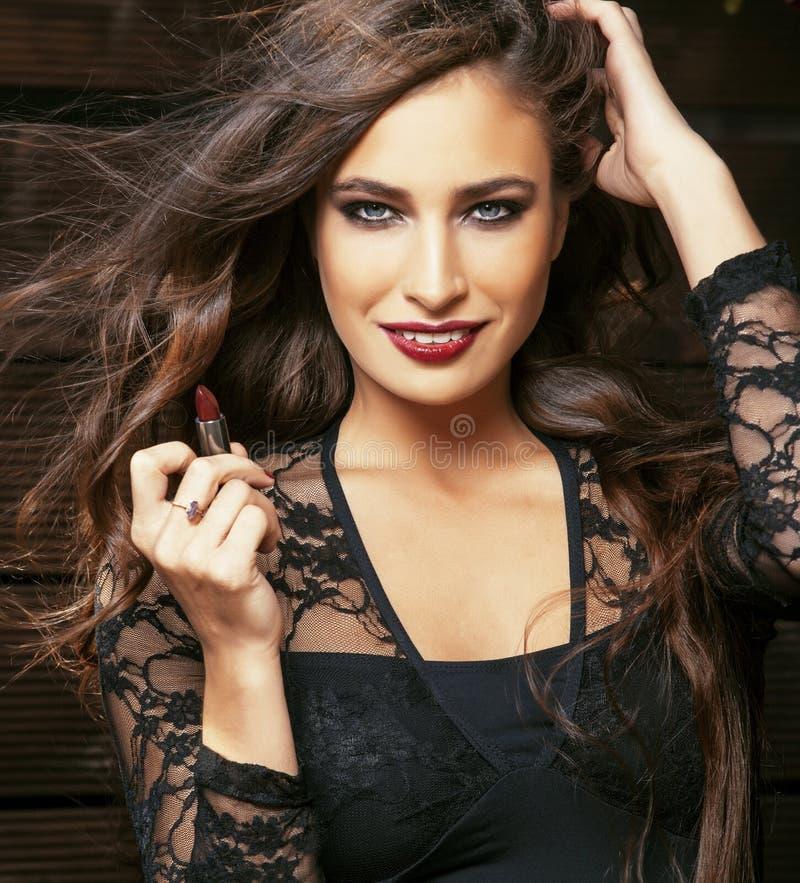Skönhet som ler den rika kvinnan snör åt in, med mörker - röd läppstift som flyger hårslut upp i inre, livsstilfolkbegreppet royaltyfria bilder