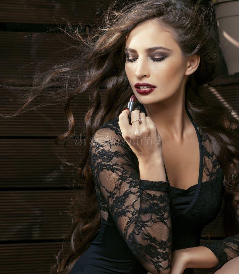 Skönhet som ler den rika kvinnan snör åt in, med mörker - röd läppstift som flyger upp hårslut fotografering för bildbyråer
