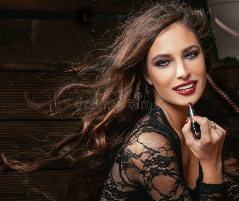 Skönhet som ler den rika kvinnan snör åt in, med rött mörker - arkivfoto