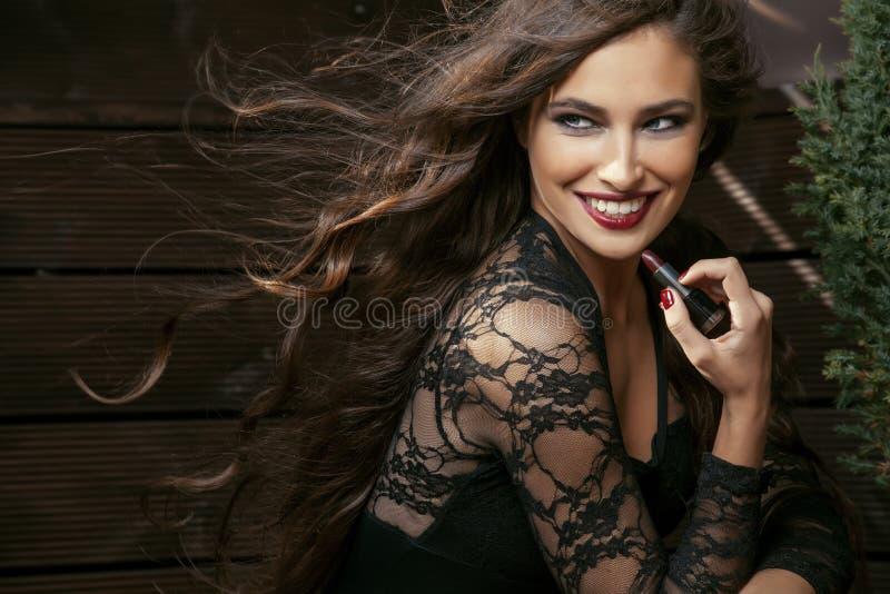 Skönhet som ler den rika kvinnan snör åt in, med rött mörker - fotografering för bildbyråer