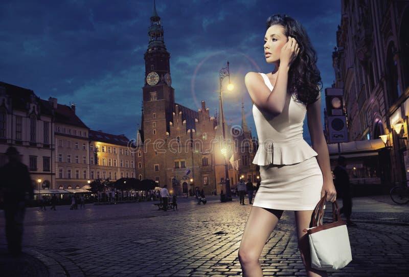 Skönhet som poserar över nattstadsbakgrund royaltyfria bilder