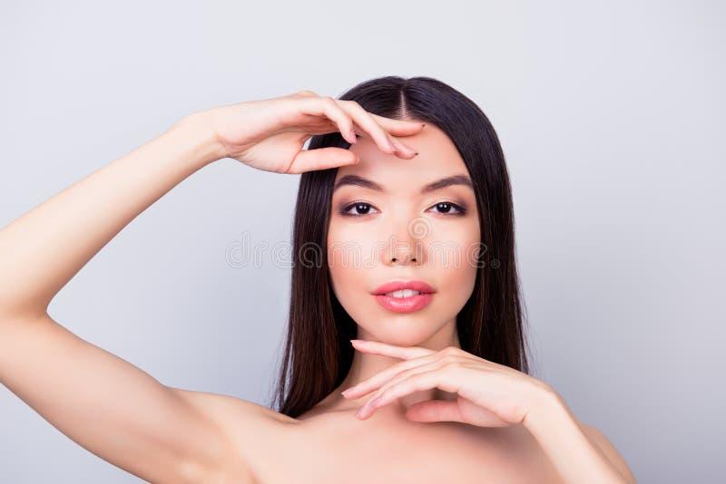 Skönhet vård- kvinnabegrepp Den unga nätta kinesiska damen är rörande försiktigt hennes attraktiva sunda hud av framsidan med fin arkivbild
