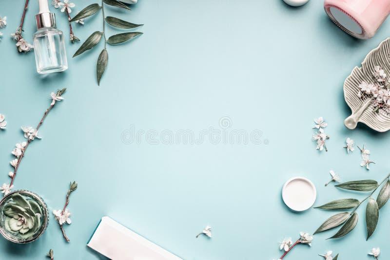 Skönhetbakgrund med ansikts- kosmetiska produkter, sidor och den körsbärsröda blomningen på pastell slösar skrivbords- bakgrund arkivbild