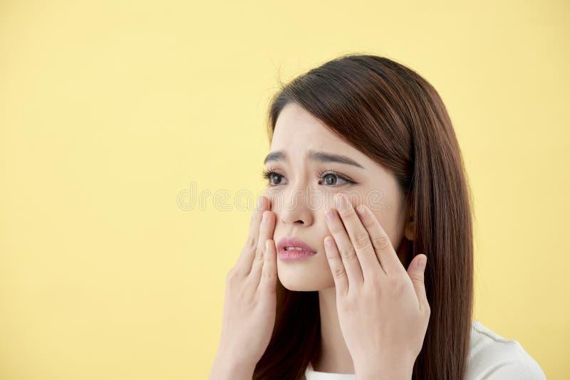 Skönhetbegrepp av den asiatiska flickan applicera genomskinlig fernissa för omsorgshud arkivbild