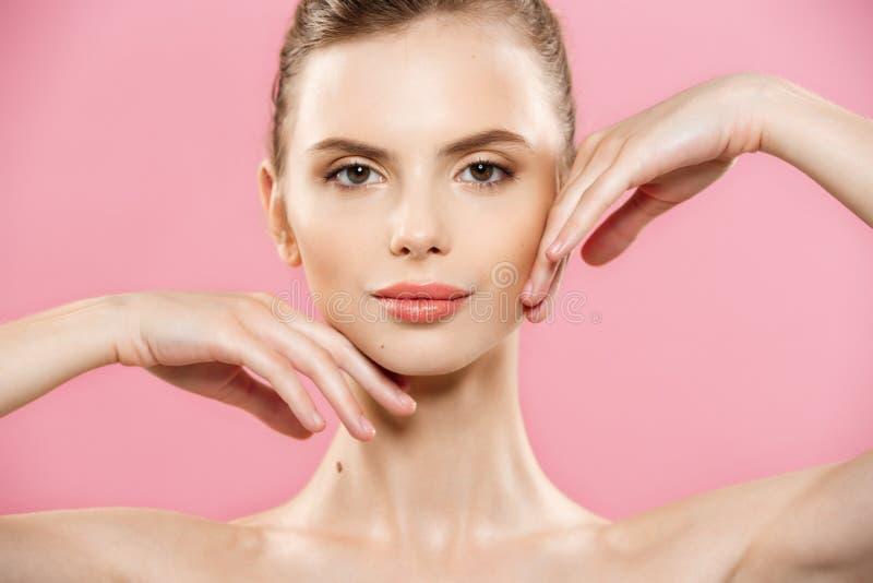 Skönhetbegrepp - nära övre stående av den attraktiva caucasian flickan med naturlig hud för skönhet som isoleras på rosa bakgrund arkivfoto