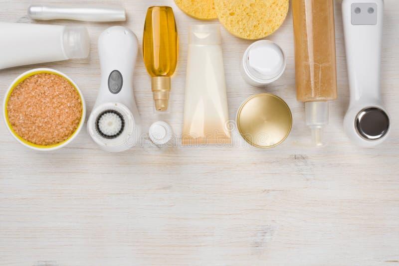 Skönhetbehandlingprodukter på träbakgrund med copyspace i botten arkivfoto