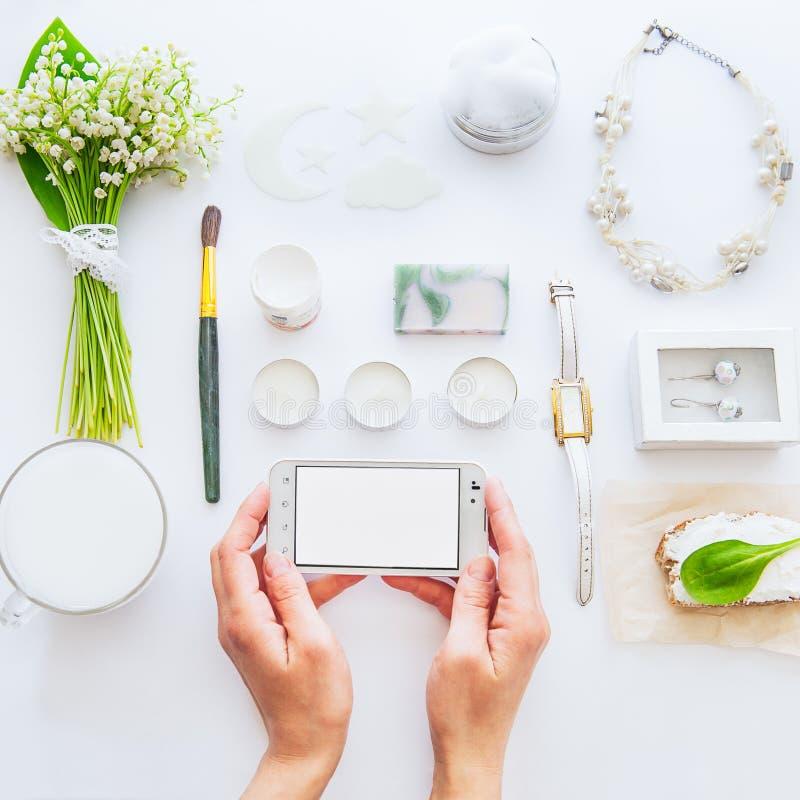 Skönhetbloggbegrepp Slutet upp kvinnliga händer håller smartphonen på bakgrunden av utformad vit datails och tillbehör för grönsk arkivfoto