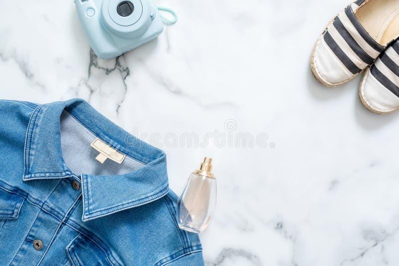 Skönhetbloggerskrivbord med kvinnlig jeans omslag, ögonblicklig fotokamera för hipster, doftande flaska av doft, trendiga randiga arkivfoton
