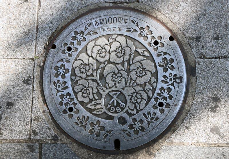 Skönhetblommamodellen av den Japan's manhålräkningen på trottoaren Japan: 100 år minnesmärke av Heisei royaltyfri fotografi