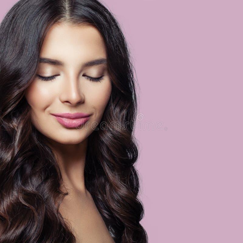 skönhetbrunettflicka Ung kvinna med långt sunt hår och rosa kantmakeup på färgrik bakgrund fotografering för bildbyråer