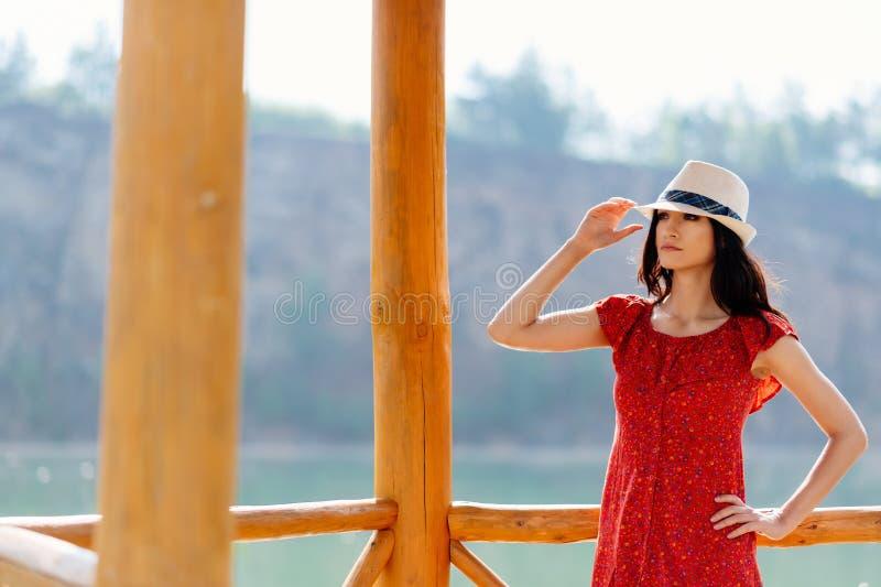 Skönhetbrunettkvinna i röd klänning och den vita solhatten över sjön royaltyfri fotografi