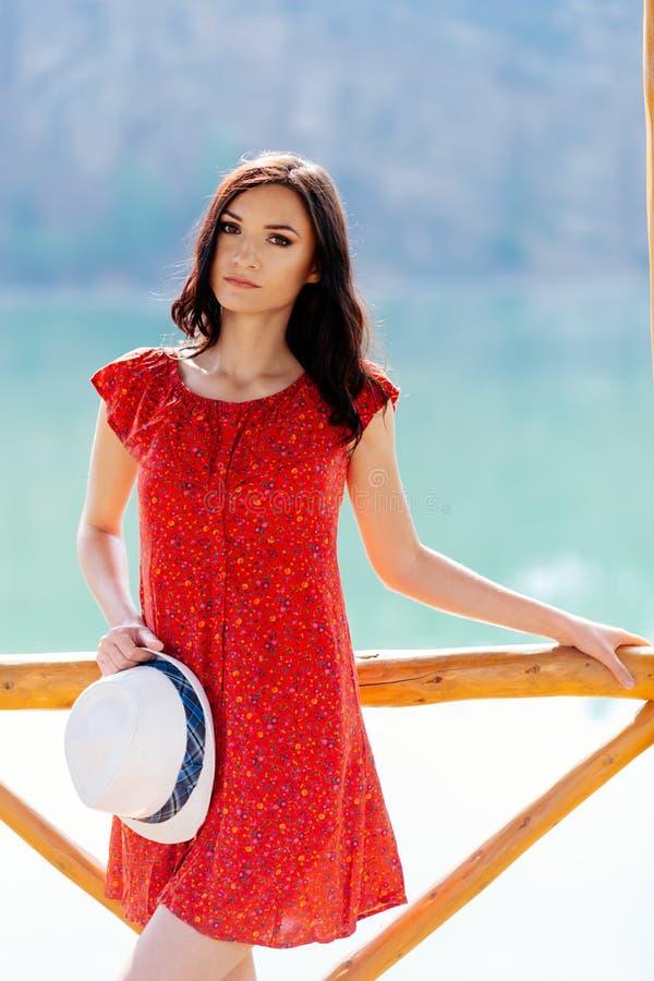 Skönhetbrunettkvinna i röd klänning och den vita solhatten över sjön arkivbilder
