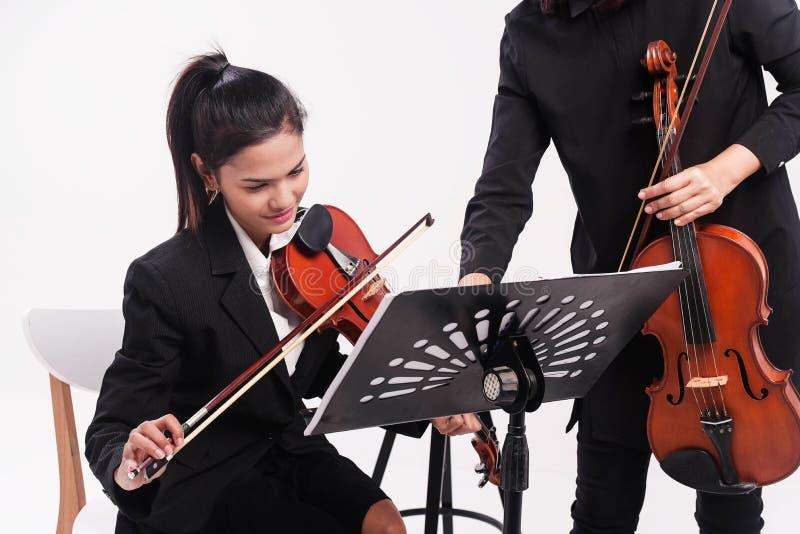 Skönhetdamen i svart likformig studerar fiolen av fiolläraren, på studiomusikrum arkivfoton
