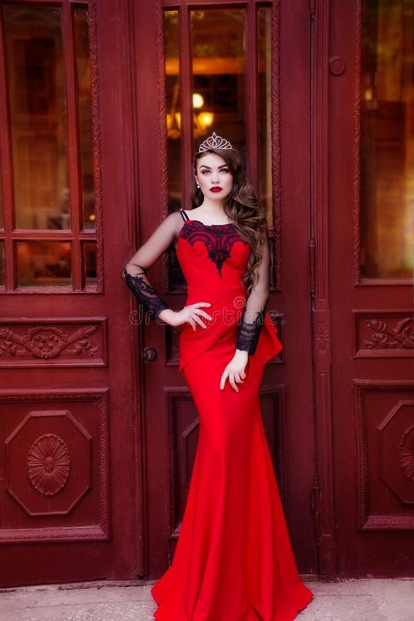 Skönhetdrottning i en röd klänning med långt hår och en tiara på hennes huvud royaltyfri bild