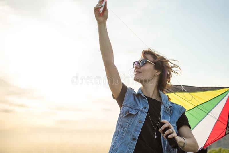 Skönhetflicka i Jean omslagsspring med draken över solnedgånghimmel svart isolerad begreppsfrihet arkivfoton