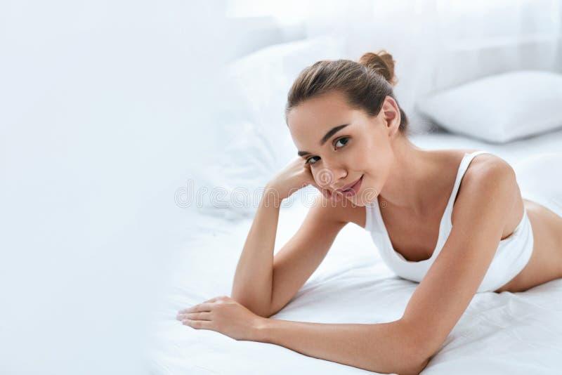 Skönhetflicka med den härliga framsidan och hud som ligger på vit säng royaltyfria bilder