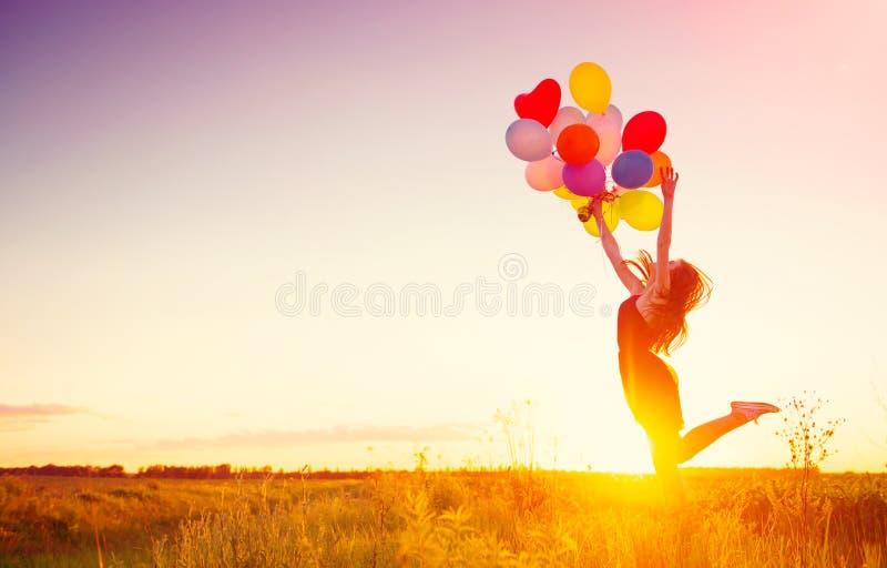 Skönhetflicka med färgrika luftballonger över solnedgånghimmel