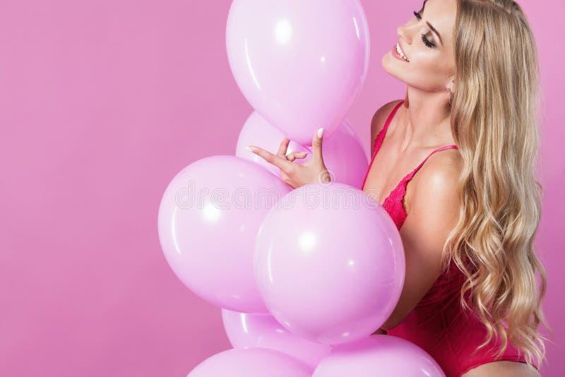 Skönhetflicka med färgrika luftballonger som skrattar över rosa bakgrund Härlig lycklig ung kvinna på födelsedagferie royaltyfri fotografi