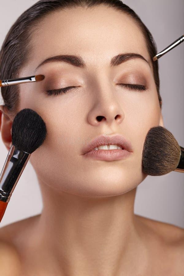 Skönhetflicka med makeupborstar härlig framsida royaltyfria bilder
