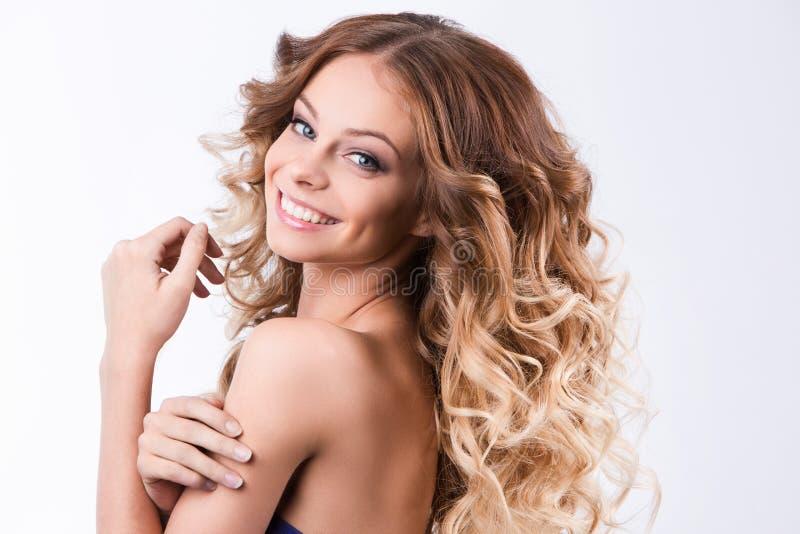 Skönhetflicka med sunt långt lockigt hår royaltyfria foton