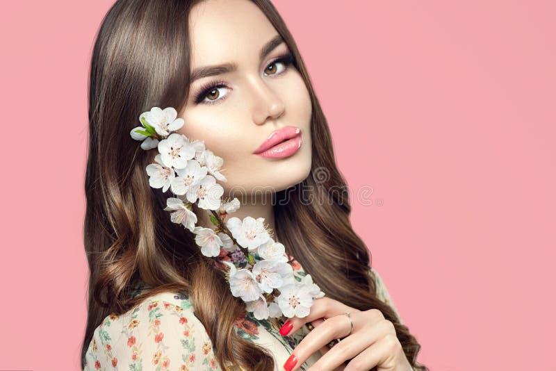 Skönhetflicka med vårsakura blommor Härlig ung kvinna med perfekt ung hud Lycklig modell som poserar med att blomma sakura arkivfoton