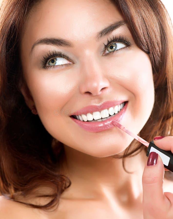 Skönhetflicka som applicerar Lipgloss arkivbild