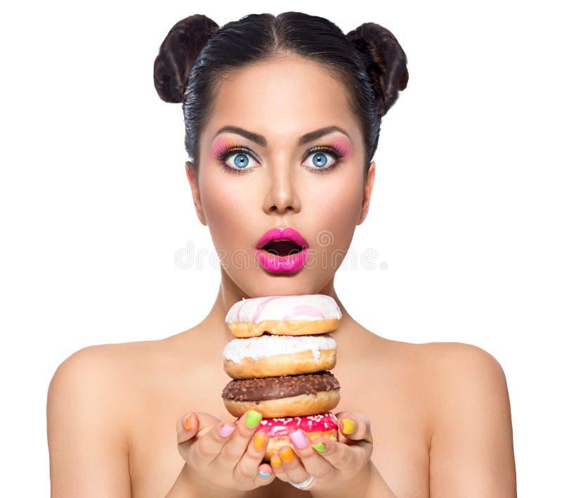 Skönhetflicka som tar bunten av färgrika donuts royaltyfri fotografi