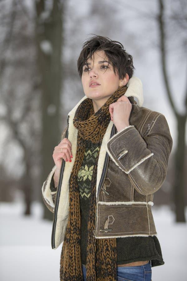 Skönhetflickan i frostig vinter parkerar utomhus Flygsnöflingor royaltyfri foto
