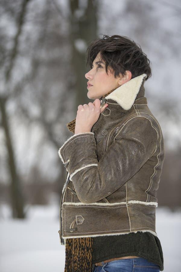Skönhetflickan i frostig vinter parkerar utomhus Flygsnöflingor arkivbild