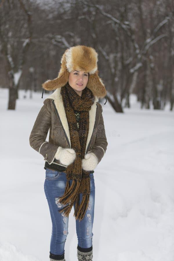 Skönhetflickan i frostig vinter parkerar utomhus Flygsnöflingor royaltyfri fotografi