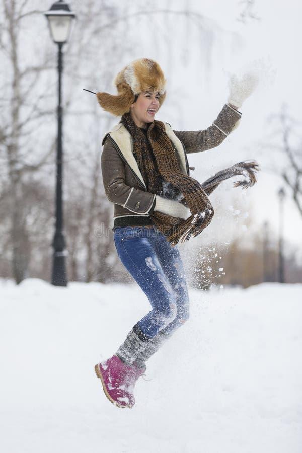 Skönhetflickan i frostig vinter parkerar utomhus Flygsnöflingor royaltyfria foton