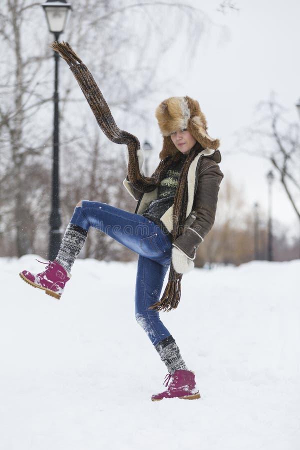 Skönhetflickan i frostig vinter parkerar utomhus Flygsnöflingor arkivfoton