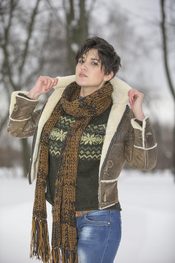 Skönhetflickan i frostig vinter parkerar utomhus Flygsnöflingor fotografering för bildbyråer